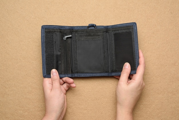 Female hands hold open empty blue textile wallet on brown background, top view
