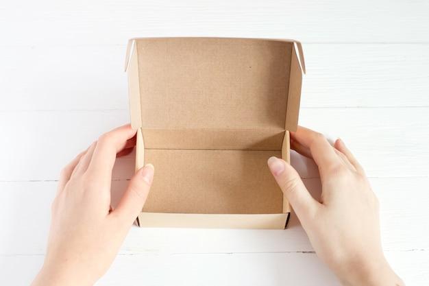 Female hands hold open empty kraft box on white wooden background