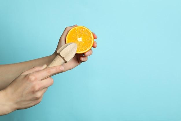 Женские руки держат апельсин и соковыжималку на синей стене