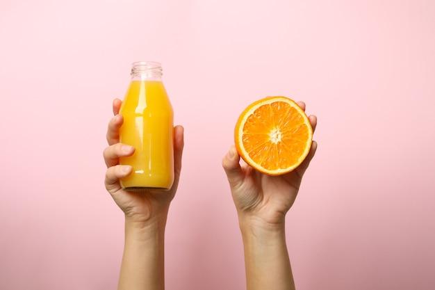 Female hands hold orange and bottle of juice on pink