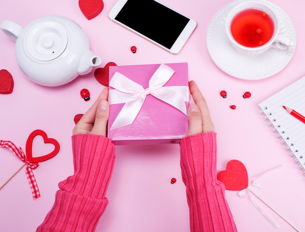 Female hands hold packed box with a pink bow