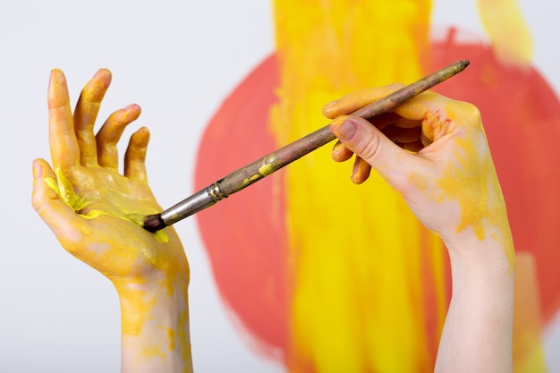 Female hands hold paint brushes painting a picture on an easel