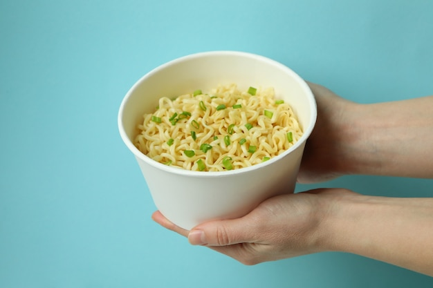 Female hands hold paper bowl with cooked noodles on blue