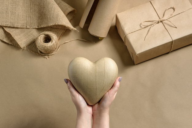 Female hands hold a paper heart on craft packaging
