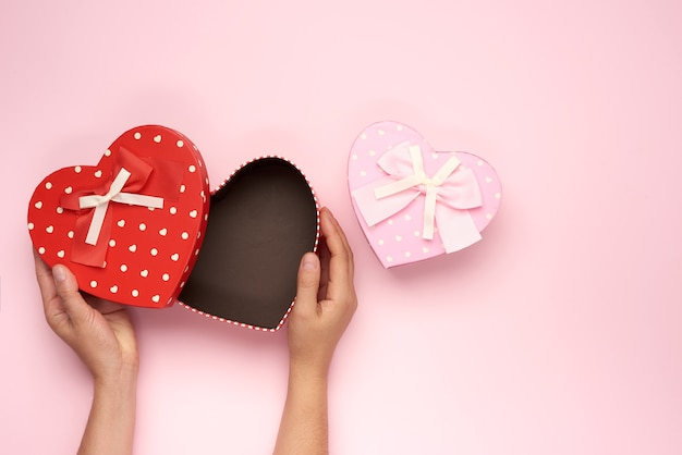 Female hands hold a paper red box in the shape of a heart