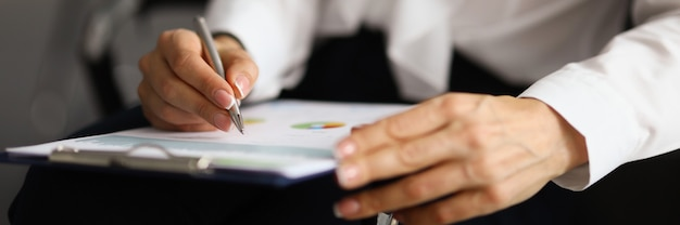 여성 손은 차트에 비즈니스 보고가 포함된 문서가 있는 펜과 클레볼드를 들고 있습니다.