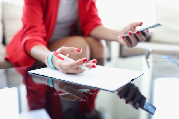 Female hands hold pen and smartphone on table are clipboard with documents