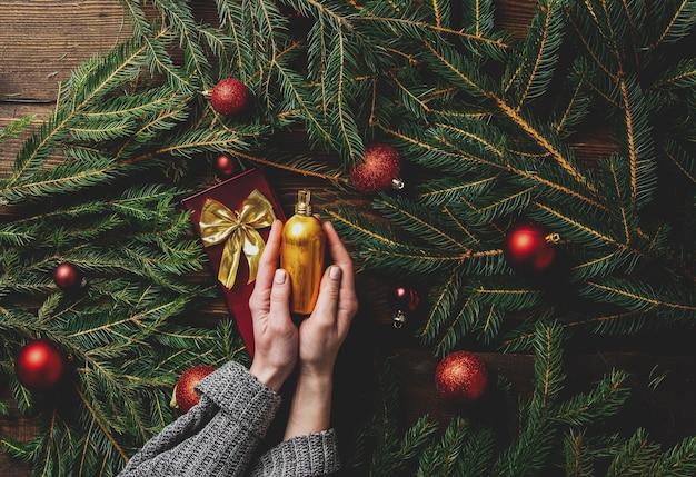 Женские руки держат флакон духов рядом с ветками елки и безделушками вокруг