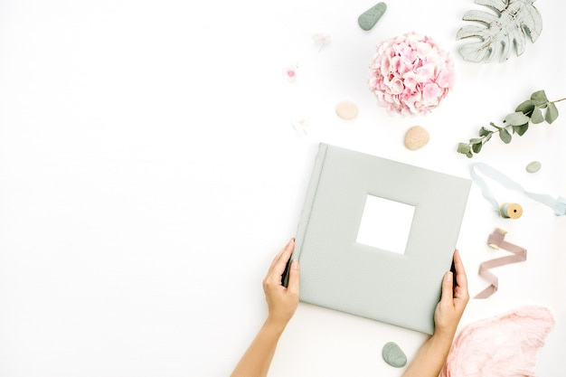 Female hands hold  photo album surrounded by different plants on white surface. flat lay, top view