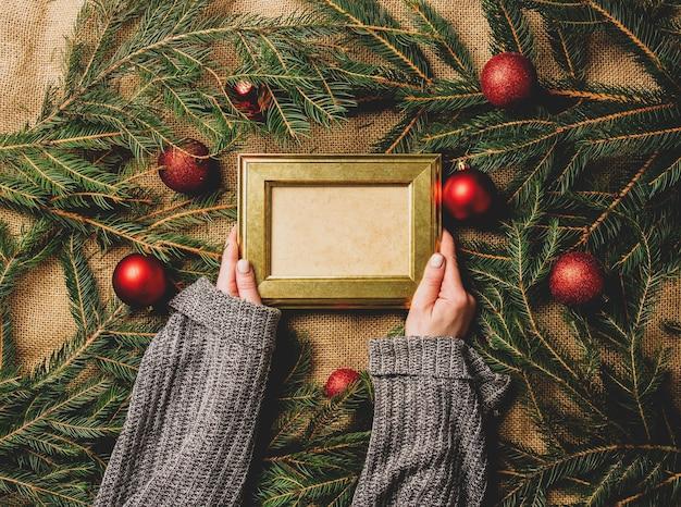 女性の手はクリスマスの装飾の横にフォトフレームを保持します