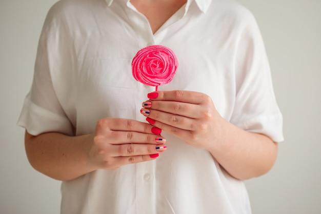 Женские руки держат розовое безе из леденцов на палочке перед белой рубашкой, аппетитный домашний десерт.