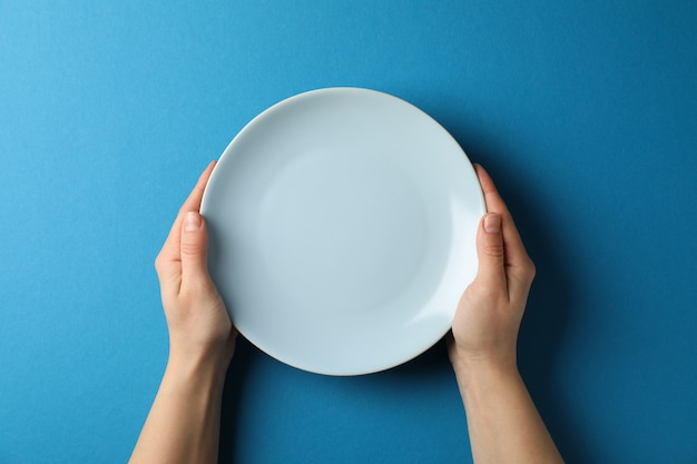 Female hands hold plate on blue background, top view