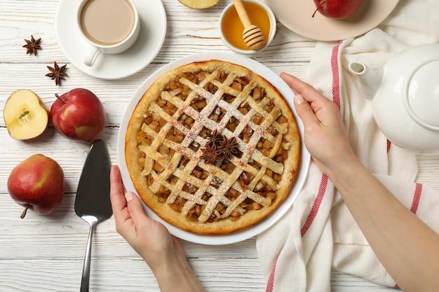 女性の手が白い木製の背景、上面にアップルパイのプレートを保持します。