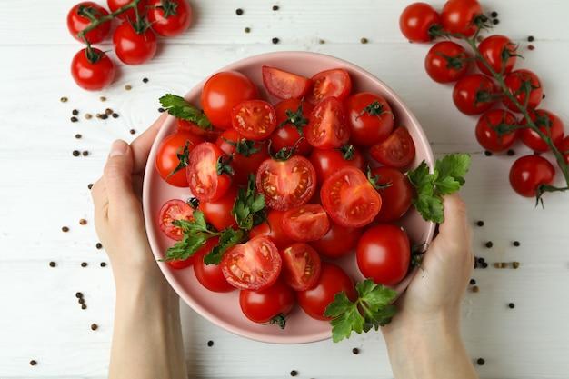 여성의 손을 잡고 나무 바탕에 체리 토마토와 접시