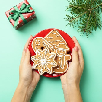 女性の手はクリスマスクッキーとプレートを保持します