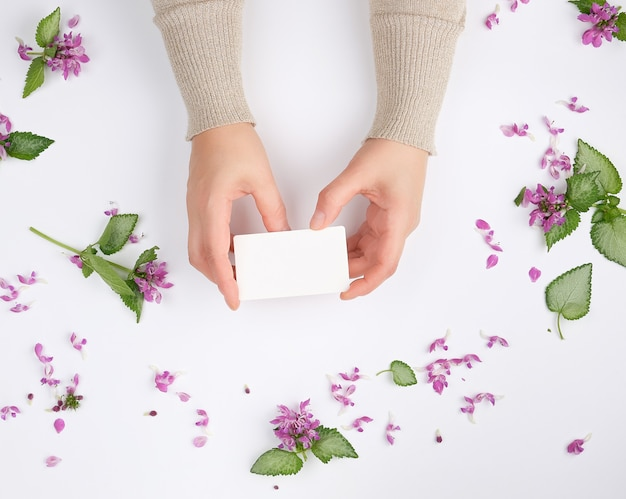 Female hands hold a rectangular blank business card over a white surface with pink flowers