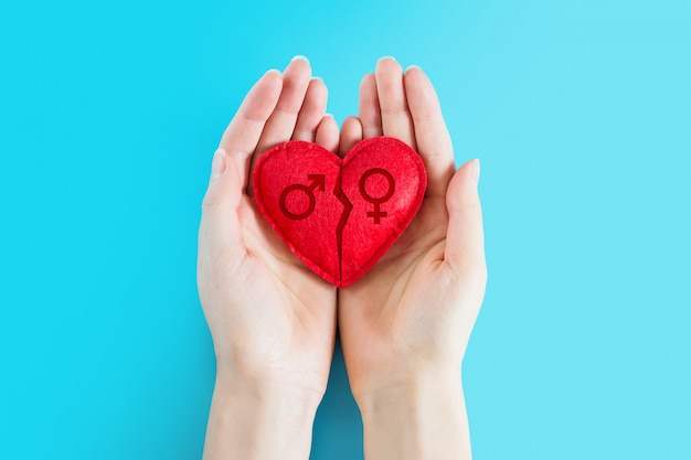 Female hands hold a red heart with a female and male symbol and a crack on a blue background. divorce, quarrel, separation, disagreement between partners concept, copy space, top view.