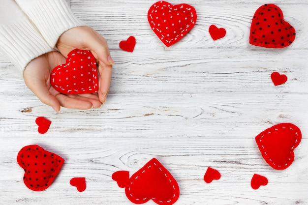 Female hands hold red heart.