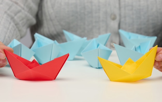 Female hands hold red and yellow paper boats on a white table. confrontation, follow a strong leader, dailog