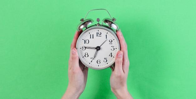 Женские руки держат ретро-будильник на зеленом