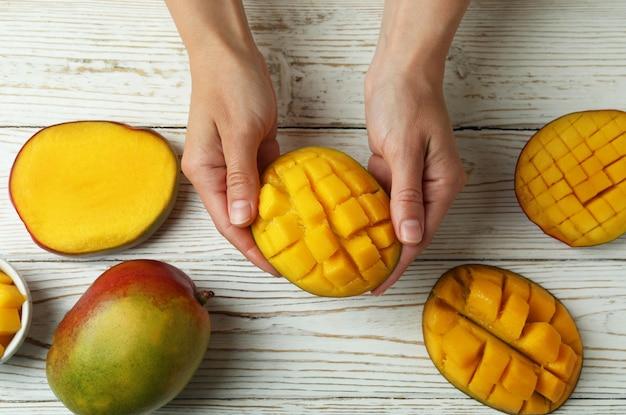 여성 손 나무 테이블에 잘 익은 망고 열매를 잡아