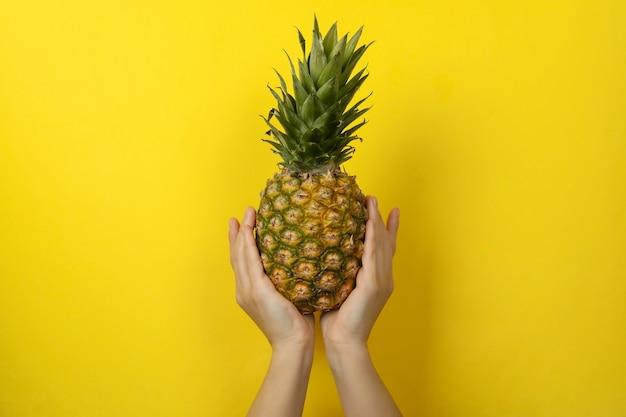 Женские руки держат спелый ананас на желтом фоне