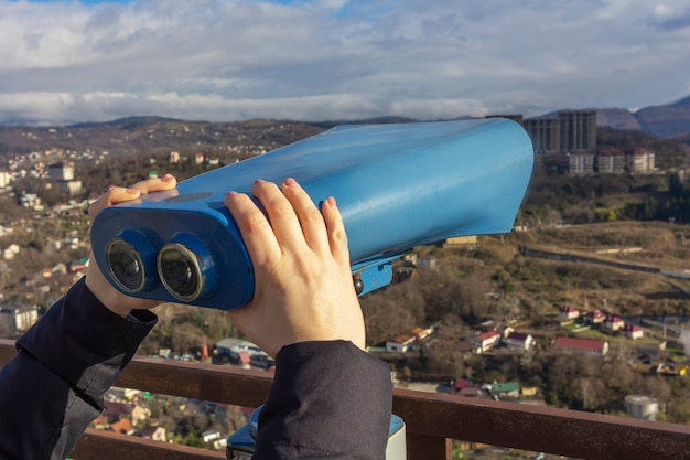 Female hands hold sightseeing touristic telescope. view from the observation deck (viewing platform) at the mountains landscape. tourist walk, excursionr text.