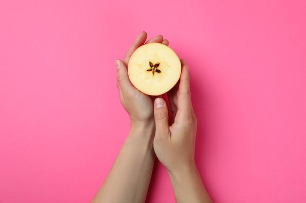 女性の手は、ピンクの背景にリンゴのスライスを保持します。