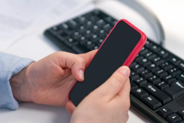Женские руки держат смартфон на фоне компьютерной клавиатуры. smm менеджер. раскрутка социальных сетей.
