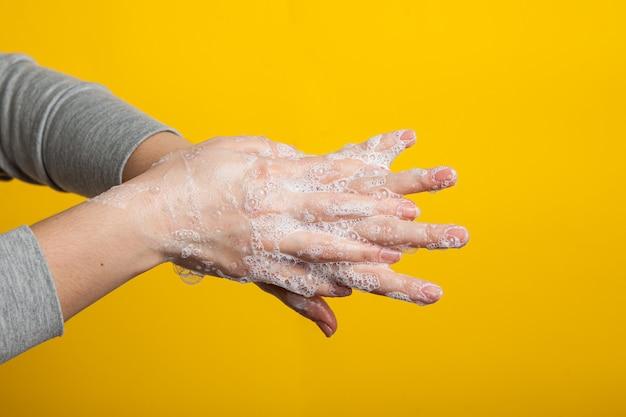 여성 손은 손가락 사이에 비누 손을 잡습니다. 적절한 손 씻기 지침. 코로나 바이러스 예방