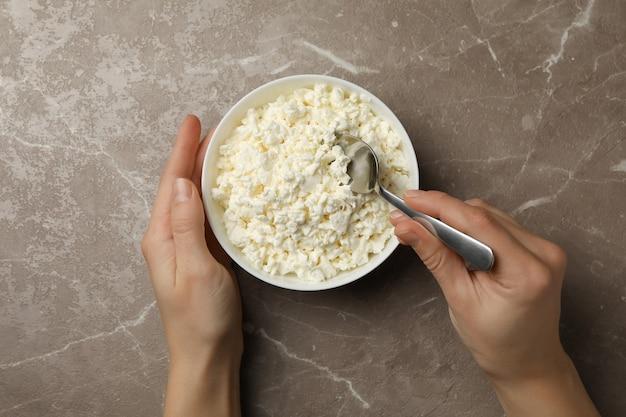 여성의 손을 잡고 코티지 치즈와 숟가락과 그릇