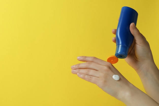Female hands hold sunscreen on yellow isolated background