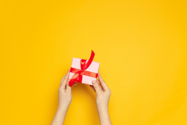 Female hands hold surprise paper box with red ribbon on yellow