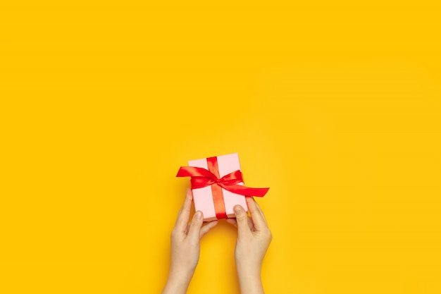 Female hands hold surprise paper box with red satin ribbon with copyspace on a yellow wall, top view, flat lay