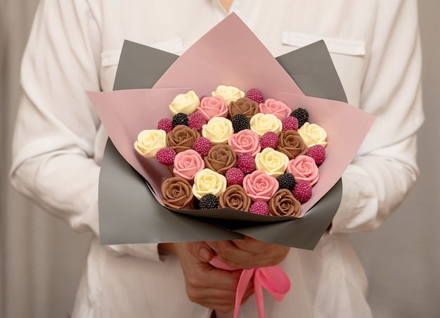 Female hands hold a sweet bouquet of chocolate roses