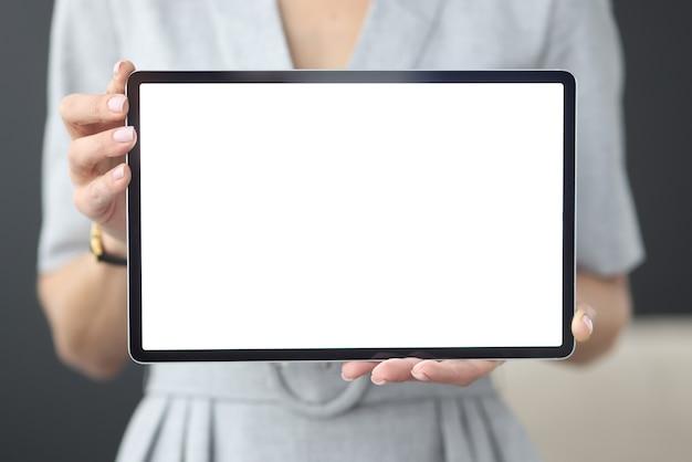 女性の手は白い画面のオンライン学習の概念を持つタブレットを保持します