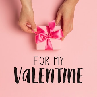 Female hands hold, take, receive a gift on a pink surface. valentine's day