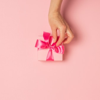 Female hands hold, take, receive a gift on a pink surface