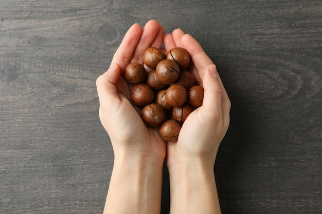 Female hands hold tasty macadamia nuts on gray wooden background