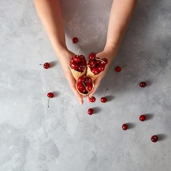 Женские руки держат три вафельные чашки с красными сладкими ягодами вишни для домашнего мороженого над серым каменным фоном, место под текстом. вид сверху. вегетарианская сырая пища.
