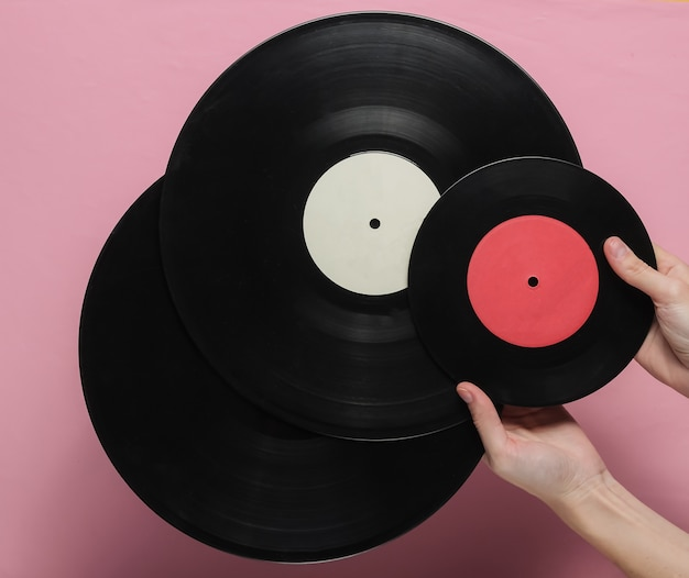 Female hands hold a vinyl record on a pink pastel background