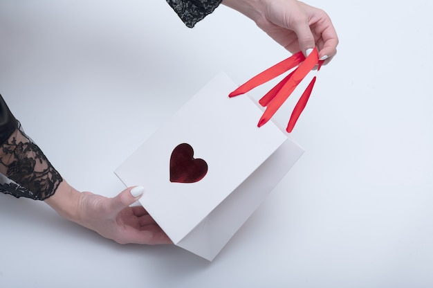 Female hands hold white bag with a symbol in the form of a heart for takeaway. on white background.