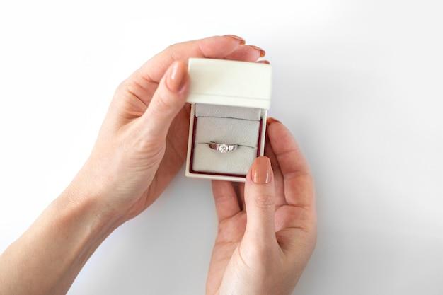 女性の手は白い背景にダイヤモンドリングと白いボックスを保持します。