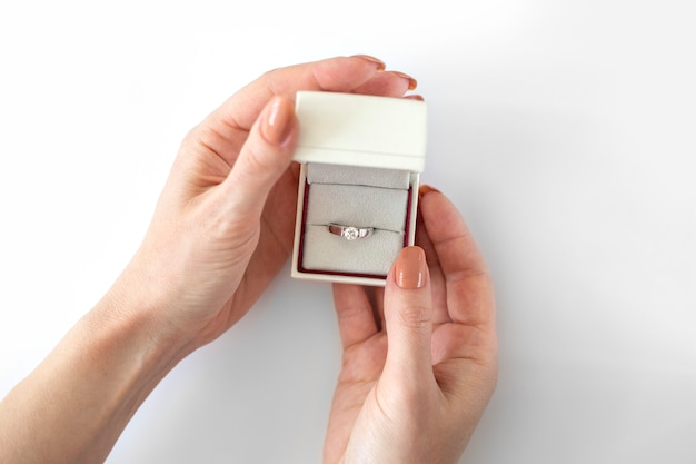 Female hands hold white box with diamond ring on white background