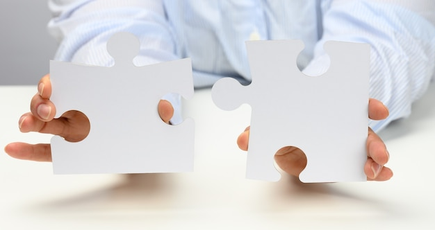Female hands hold white large paper puzzles. solution concept, strategy and goal achievement