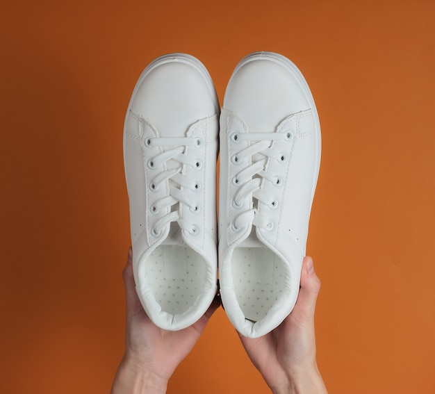 Female hands hold white stylish sneakers on brown studio paper