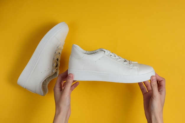 Female hands hold white stylish sneakers on a yellow studio paper