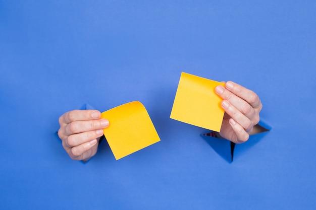Женские руки держат желтые бумажные палочки на синем фоне. женские вставлены в бумажный фон. место для надписи.