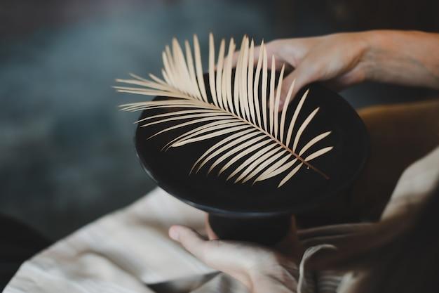 Женские руки держат черную керамическую тарелку, украшенную крупным планом листьев папоротника