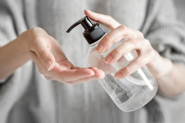 Женские руки держат флакон с антисептическим гелем и используют антибактериальный спирт для гигиены и мытья рук от короновируса